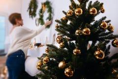 De jonge vrouw verfraait de Kerstmisboom creërend de vakantieatmosfeer Stock Afbeeldingen