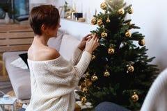 De jonge vrouw verfraait de Kerstmisboom creërend de vakantieatmosfeer Royalty-vrije Stock Foto's