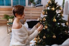 De jonge vrouw verfraait de Kerstmisboom creërend de vakantieatmosfeer Stock Foto