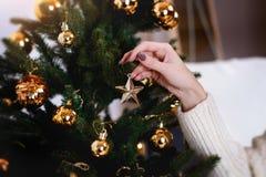 De jonge vrouw verfraait de Kerstmisboom creërend de vakantieatmosfeer Royalty-vrije Stock Afbeelding
