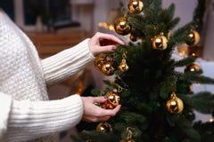 De jonge vrouw verfraait de Kerstmisboom creërend de vakantieatmosfeer Stock Foto's