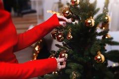 De jonge vrouw verfraait de Kerstmisboom creërend de vakantieatmosfeer Royalty-vrije Stock Afbeeldingen