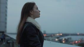 De jonge vrouw verheugt zich op avondstad scape stock videobeelden