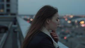 De jonge vrouw verheugt zich op avondstad scape stock video
