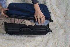 De jonge vrouw verzamelt een koffer De reiziger die voor reis, persoonlijke perspectiefmening voorbereidingen treffen dat neem va stock foto