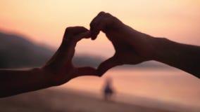 De jonge vrouw vormt hart met overhandigt de zonsondergang door de oceaan met uit nadrukkinderen Langzame Motie 1920x1080 stock videobeelden