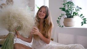 De jonge vrouw vrij van allergieën houdt boeket van veergrassen in pyjama op bed glimlachend op camera stock videobeelden