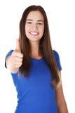De jonge vrouw in vrijetijdskleding het gesturing beduimelt omhoog. Royalty-vrije Stock Fotografie