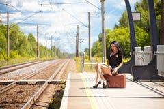 De jonge vrouw wacht op een trein Stock Fotografie