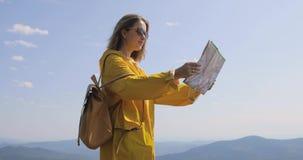 De jonge vrouw wandeling in regenjas op een bergsleep, houdt en controleert kaart richtingen tegen De wandelaar bereikt bergboven stock footage