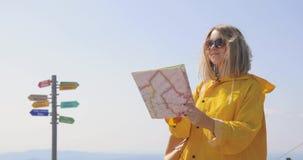 De jonge vrouw wandeling in regenjas op een bergsleep, houdt en controleert kaart richtingen tegen De wandelaar bereikt bergboven stock videobeelden