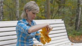 De jonge vrouw weeft een kroon van esdoornbladeren in het park stock video