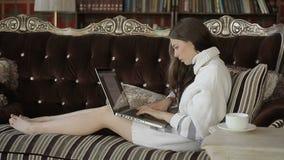 De jonge vrouw werkt aan haar laptop, terwijl het zitten op een luxebank stock videobeelden