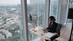 De jonge vrouw werkt in een modern gevestigd bureau aan een hoge vloer van een wolkenkrabber Bedrijfsvrouw die aan laptop werken  stock videobeelden