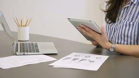De jonge vrouw werkt, gebruikend tablet terwijl het zitten bij lijst in huis stock video
