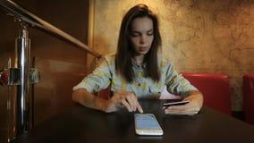 De jonge vrouw werkt met de celtelefoon Het wijfje draait of typt het krediet of debetkaartaantal stock footage
