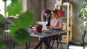 De jonge vrouw werkt met laptop zitting bij lijst in bureau Haar collega komt, vrouwenbegin het letten op het scherm stock footage