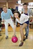 De jonge vrouw werpt bal in kegelen stock foto