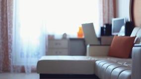 De jonge vrouw werpt kleding op bank in woonkamer in vroege ochtend stock footage