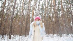 De jonge vrouw werpt omhoog sneeuw met een aardige glimlach in het de winterbos stock footage