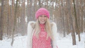 De jonge vrouw werpt omhoog sneeuw met een aardige glimlach in het de winterbos stock video