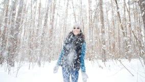 De jonge vrouw werpt omhoog sneeuw met een aardige glimlach in het de winterbos stock videobeelden