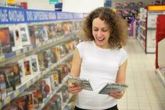 De jonge vrouw in winkel kiest schijf Stock Foto
