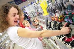 De jonge vrouw in winkel speelt met bedieningshendel Royalty-vrije Stock Afbeelding