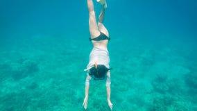 De jonge vrouw in wit chemise en zwart zwempak duikend in de oceaan om de bodem te bereiken Vrouwelijke duiker die zwemmen en stock video