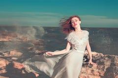 de jonge vrouw in witte fladderende kleding bevindt zich op de overzeese kust dichtbij de grote steen Royalty-vrije Stock Foto's