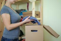 De jonge vrouw zet kleren aan kartondoos royalty-vrije stock afbeeldingen