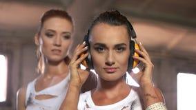 De jonge vrouw zet op bouwhoofdtelefoons stock video