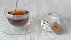 De jonge vrouw zet xylitol van het suikersubstituut in een kop thee, close-up stock footage