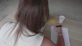 De jonge vrouw zit bij lijst met laptop met het groene scherm en types voorbereidend plan op dag stock video
