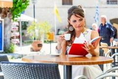 De jonge vrouw zit in de koffie Stock Fotografie