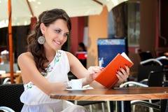 De jonge vrouw zit in de koffie Stock Foto's