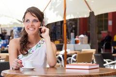 De jonge vrouw zit in de koffie Royalty-vrije Stock Foto