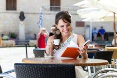 De jonge vrouw zit in de koffie Stock Foto
