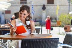 De jonge vrouw zit in de koffie Royalty-vrije Stock Afbeelding