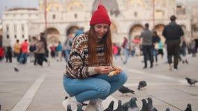 De jonge vrouw zit in het vierkant en voedt de duiven met handen stock videobeelden