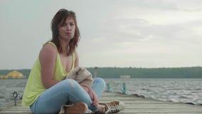 De jonge vrouw zit in lotusbloem stelt op oude houten pijler en bekijkt droevig camera stock videobeelden