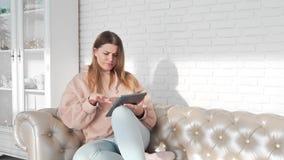 De jonge vrouw zit op de bank en de brandingen Internet in de tablet, online betalingen, online helper, handigheid van stock footage