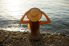 De jonge vrouw zit op de kiezelsteenkust met strandkleding bij het houden van een strohoed op haar hoofd Achtermeningsportret van Royalty-vrije Stock Foto's