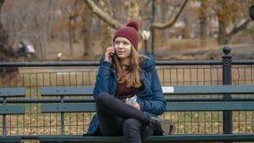 De jonge vrouw zit op een bank in Central Park New York royalty-vrije stock foto
