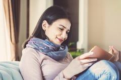 De jonge vrouw zit op een bank en leest een boek royalty-vrije stock afbeelding