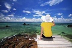 De jonge vrouw zit op een brug over strand Royalty-vrije Stock Foto's