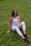 De jonge vrouw zit op gras Royalty-vrije Stock Afbeelding