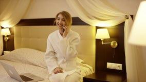 De jonge vrouw zit op het bed naast haar laptop en spreekt op de telefoon stock video