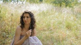 De jonge vrouw zit op het gras en de glimlach stock videobeelden