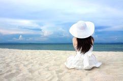 De jonge vrouw zit op het strand Stock Fotografie